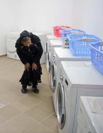 Une femme pose devant les machines à laver